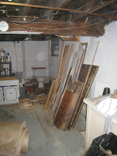 The basement bathroom, torn apart (and extra lumber ready to be used in future projects).