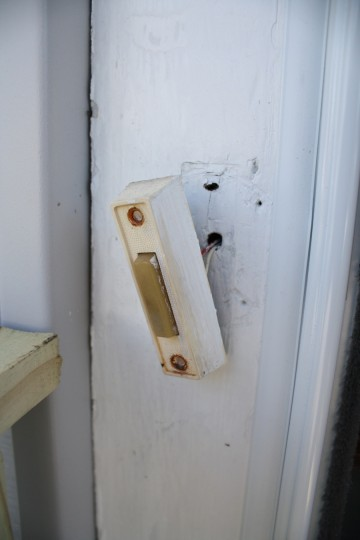 Old discolored doorbell, unattached.
