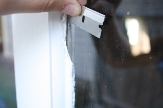Using a razor blade to clean paint from the glass panes.