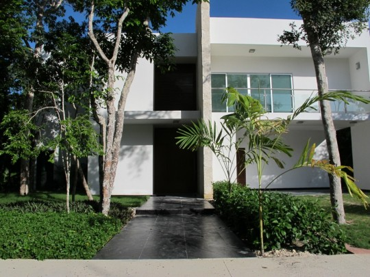 Well-designed home, with a pretty black stone walkway.