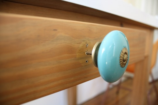 New knob, new drilled hole, and can you tell where the wood had been protected by the previous drawer pull? Odd.