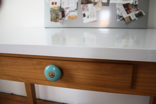 Ooh, shiny desk. New knob. Pop of color.