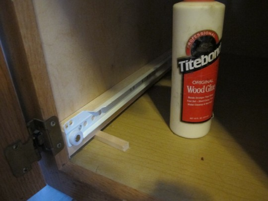Little pieces of scrap wood shim the sliders up just enough to clear the cabinet threshold.