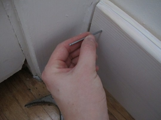 Nail through the pilot hole into the stud.
