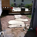 Installing the first row of flagstones, the main walkway from the deck to the garage.