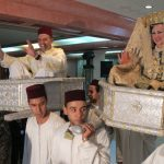 The bride and groom were both carried while she wore her 4th dress and he wore traditional Moroccan attire.