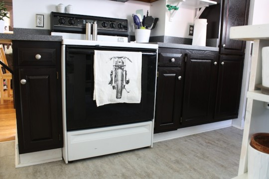 Kitchen cabinets, refinished with dark brown stain and adorned with a new tea towel.