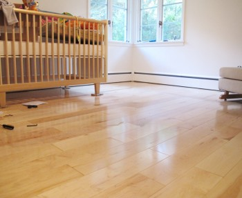 Our bright nursery with beautiful maple hardwoods and white, clean walls.