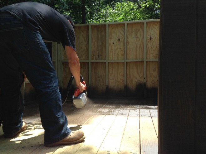 Staining the floors of our treehouse with a sprayer.