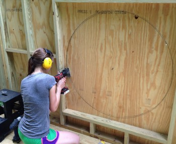 Cutting a circle into T1-11 for the kid's treehouse modern window.
