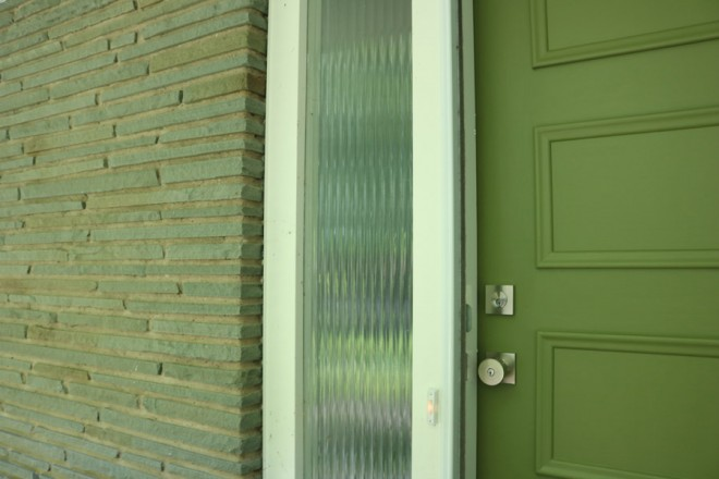 Painting a front door a mossy green to coordinate with flagstone facade.