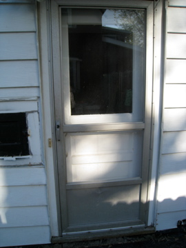 The side door pre-painting, pre-siding. How old is this dinged, fragile metal door?