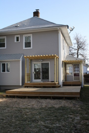 Back deck, pergolas, new siding, and dead grass.
