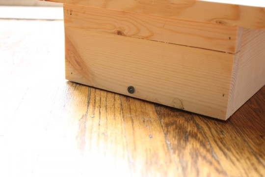 A single screw holds a removable floorboard in place so that it can be dropped down for cleaning purposes.