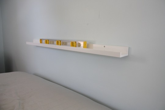 A floating IKEA shelf to support the new guest room headboard.