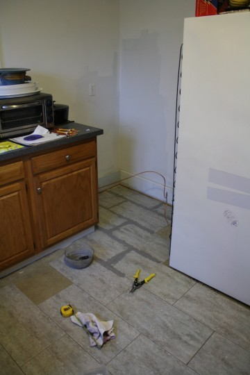 Tiling and grouting behind where the fridge would sit.