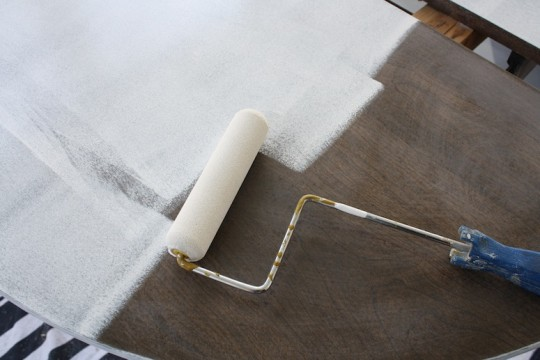 Priming the laminate surface with high adhesion water-based primer.
