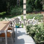 Beneath the pergola, a pretty CB2 table, and just beyond the pergola, a built-in fire pit in their flagstone patio.