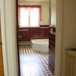 View into the bathroom from the hallway. Very maroon.