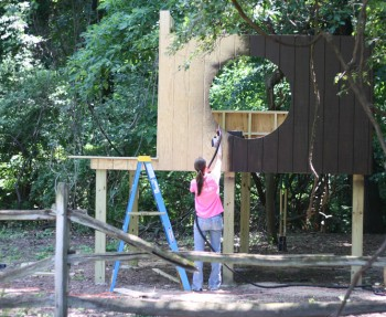 Spraying stain onto our t1-11 treehouse panels.